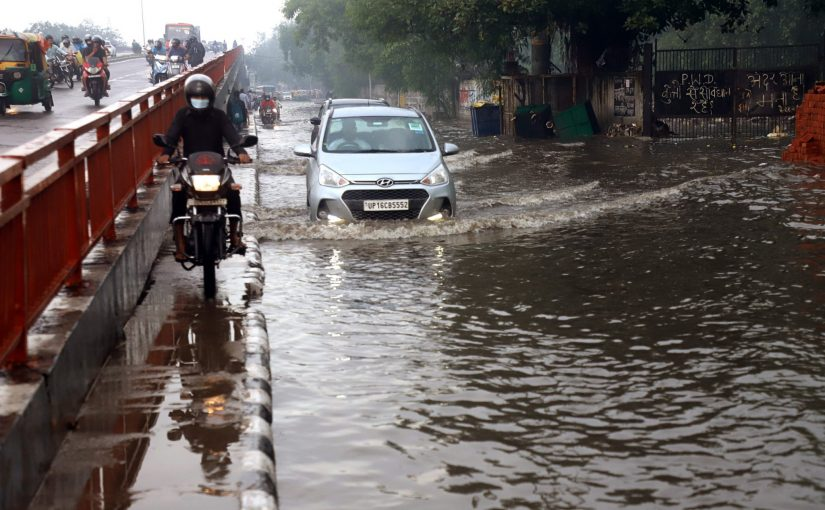 A biker rides on the pavement to avoid a waterlogged road following heavy rainfall at Mandoli